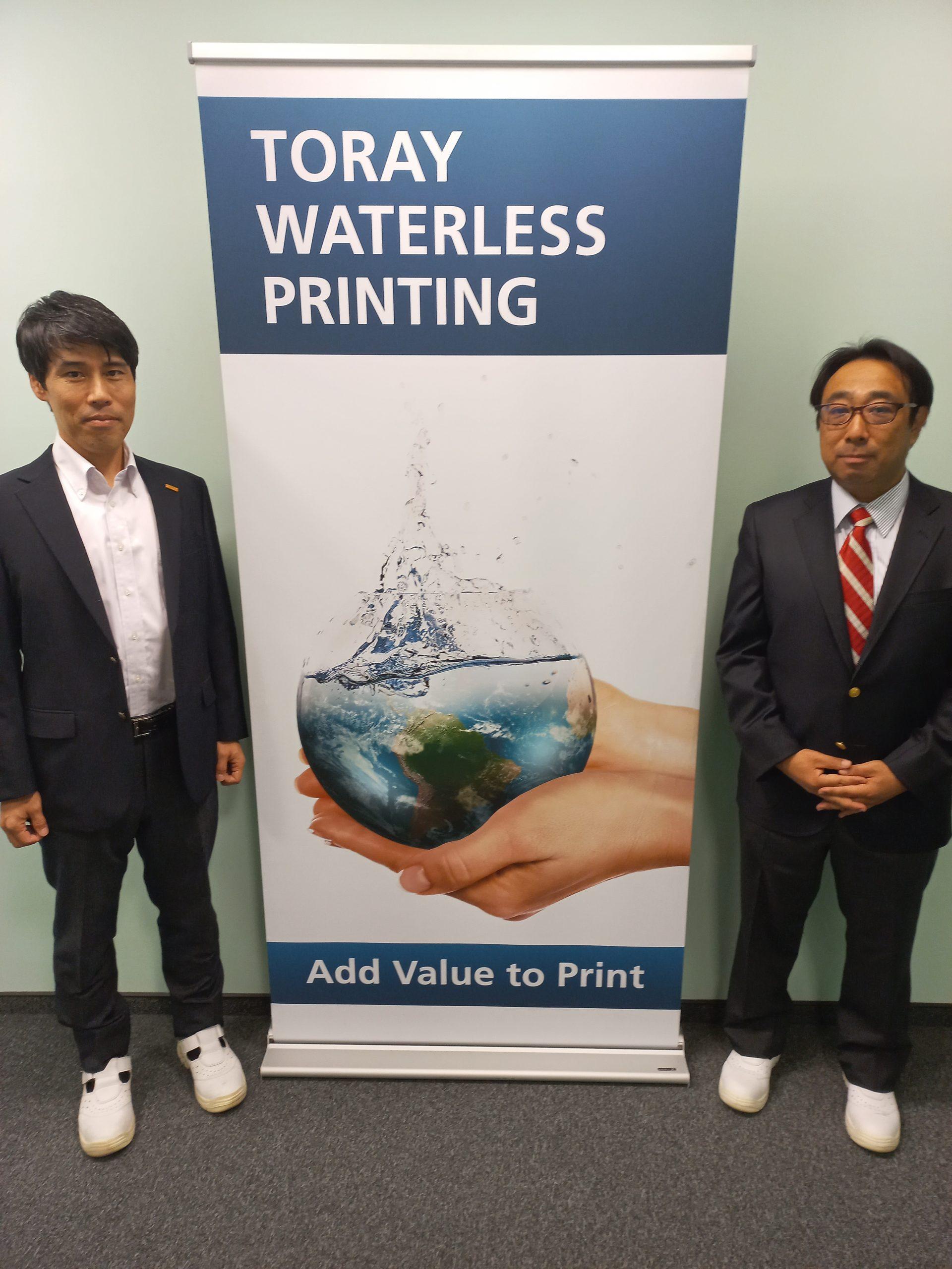 Mr. Kaoru Ueda and Mr. Junichi Ishii posing before a Toray banner